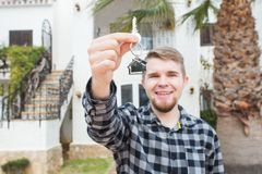 Property, ownership, new home and people concept - young man with keys standing outside new home stock image