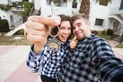 Property, real estate and apartment concept - Happy funny young couple showing a keys of their new house.  royalty free stock photos