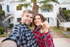 Property, real estate and apartment concept - Happy funny young couple showing a keys of their new house stock image