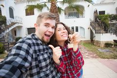 Property, real estate and apartment concept - Happy funny young couple showing a keys of their new house.  stock photo