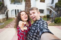 Property, real estate and rent concept - Happy funny young couple showing a keys of their new house. Property, real estate and rent concept - Happy smiling young royalty free stock photos