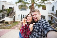 Property, real estate and rent concept - Happy funny young couple showing a keys of their new house royalty free stock image