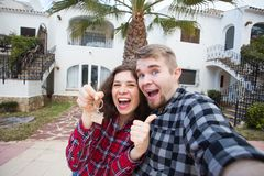 Property, real estate and rent concept - Happy funny young couple showing a keys of their new house. Property, real estate and rent concept - Happy smiling young stock photos