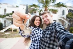 Property, real estate and rent concept - Happy smiling young couple showing a keys of their new house.  royalty free stock images