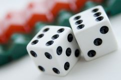 Property Risk. Two dice show six and six in front of a row of plastic housing (shallow depth of field used Royalty Free Stock Photos