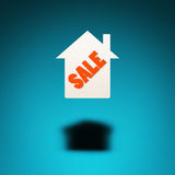 Property For Sale. An icon of a house hovers in the air, casting a shadow on blue background. The word `sale` is inscribed in the silhouette of the house Stock Photography