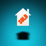 Property for sale. An icon of a house hovers in the air, casting a shadow on blue background. The word `sold` is inscribed in the silhouette of the house Stock Image