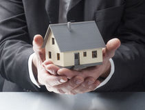 Property for sale by real estate agent. Male hands showing a house Stock Images