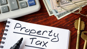 Property tax written in a notebook. Property tax written in a notebook and calculator Royalty Free Stock Images