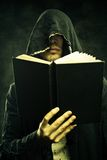 Prophet of post apocalyptic world. Portrait of sinister cultist in hood with book Royalty Free Stock Photos