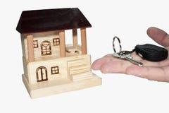 Propiedades inmobiliarias y mano con la llave Fotografía de archivo