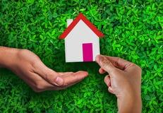 Propiedades inmobiliarias y vivienda de la publicidad de la cubierta del daño con la mano de la mujer que sostiene la casa de pap foto de archivo