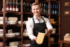Propietario de negocio con queso en tienda fotos de archivo