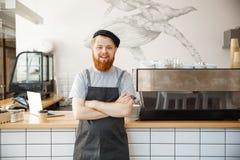 Propietario de negocio Concept - retrato del café del barista caucásico barbudo joven feliz en delantal con la mirada confiada foto de archivo