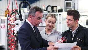 Propietario de negocio en fábrica que discute el componente con el equipo de la ingeniería almacen de video
