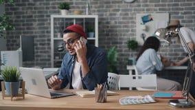 Propietario de negocio que hace llamada con el smartphone que se sienta en el escritorio en oficina creativa almacen de metraje de vídeo