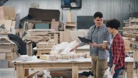 Propietarios de negocio que hablan en el taller de madera que sostiene el café, los papeles y la tableta metrajes