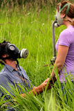 Proposal. A young man in love asking for the hand of his girlfriend, wearing gas masks in a field of tall grass. Bad breath, allergies, or the Apocalypse? Stock Photography