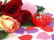 Proposal. Wedding rings sit atop a red plastic box. Three roses lay next to it, various heart shapes scattered around Stock Photos