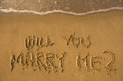 Proposal. Will you marry me written in sand, water approaching Royalty Free Stock Photography