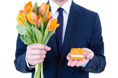 Proposal - man holding gift box and flowers. Proposal - man holding gift box with wedding ring and flowers isolated on white background Royalty Free Stock Photos