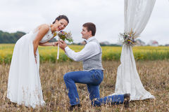 Proposal moment on happy wedding day of young newlywed couple. Stock Photos