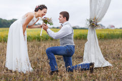 Proposal moment on happy wedding day of young newlywed couple. Royalty Free Stock Images