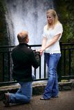 Proposal by Waterfall. A young man kneeling and proposing in front of a waterfall. Shallow depth of field Royalty Free Stock Photos