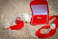 Propose at the beach. Engagement ring is placed on a white sand beach with a red ribbon Stock Images