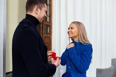 Propose of marriage. A men makes a marriage proposal to his girlfriend outdoors royalty free stock photo