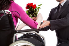 Proposing to disabled. A man proposing to a disabled woman on a wheelchair Stock Photography