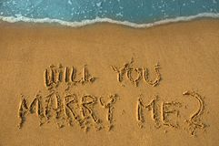 Proposition. Will you marry me written in sand, cyan water Stock Photos