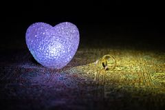 Proposition de mariage avec les anneaux et le coeur de mariage d'or Concept de Valentine Fond brumeux modifié la tonalité foncé Photos stock