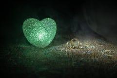 Proposition de mariage avec les anneaux et le coeur de mariage d'or Concept de Valentine Fond brumeux modifié la tonalité foncé Photo stock