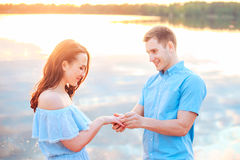 Proposition de mariage sur le coucher du soleil le jeune homme fait une proposition des fiançailles à son amie sur la plage Images stock