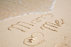 Proposition on the sand. Marry me written on the white sandy beach Stock Photos