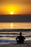 Proposito di seduta della spiaggia di tramonto di alba dell'uomo Immagine Stock
