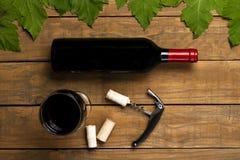 Proppar för exponeringsglas för vinflasköppnare och vinrankasidor på träbakgrund Bästa sikt med kopieringsutrymme royaltyfri bild