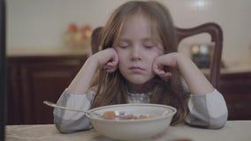 Propped de kleine ongelukkige het meisjeszitting van het close-upportret voor ouders omhoog haar hoofd kijkend in de camera Jonge stock footage
