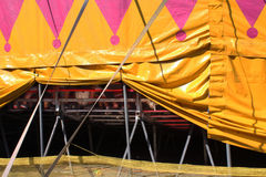 Propped up side of a circus tent. With feet of spectators in bleachers Royalty Free Stock Photos