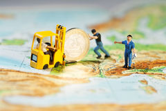 Propping Up The Euro. Team of tiny miniature figurines  and loading it on to a forklift, map of Europe concept Stock Photos