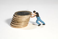 Propping Up The Euro. A miniature workman figurine propping up a pile of Euro coins with his hands Royalty Free Stock Photo