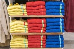 Propra buntar av vikta kläder på shoppa bordlägger Färgvikningskjorta i ett trevligt organiserat bekläda lager royaltyfri fotografi
