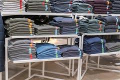 Propra buntar av vikta kläder på shoppa bordlägger Färgvikningskjorta i ett trevligt organiserat bekläda lager arkivfoto