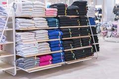 Propra buntar av vikta kläder på shoppa bordlägger Färgvikningskjorta i ett trevligt organiserat bekläda lager arkivfoton