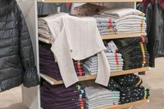 Propra buntar av vikta kl?der p? shoppa bordl?gger F?rgvikningskjorta i ett trevligt organiserat bekl?da lager arkivbilder