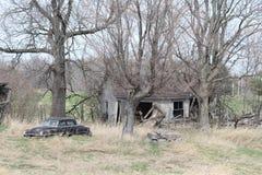 Propriété abandonnée avec la voiture et les bâtiments Images stock