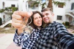 Propriété, immobiliers et concept de loyer - jeune représentation drôle heureuse de couples clés de leur nouvelle maison photos stock