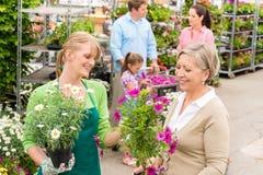 Propriétaire aux fleurs mises en pot de achat de jardinerie Photos stock
