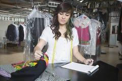 Propriétaire avec le bloc-notes vérifiant des vêtements au compteur photographie stock libre de droits